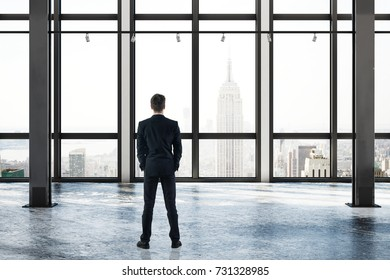 Back view of young businessman in empty concrete room interior with New York city view and daylight. Research concept. 3D Rendering