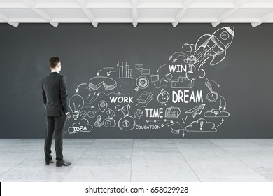 Back view of young businessman looking at wall with business sketch in interior. Entrepreneurship concept. 3D Rendering