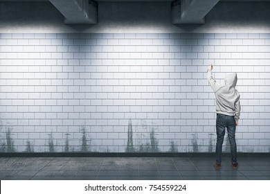Back view of young hipster man with hood painting graffiti in subway station. Vandalism concept. Mock up, 3D Rendering