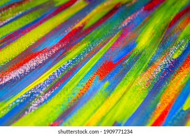 Background from different strokes of red, yellow, green and blue paint with brush close-up. Bright colorful backdrop of colored brush lines. Mixing color streaks of paint with cracked and scratched.