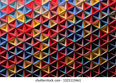 Background with randomly colored red blue yellow geometric shapes - small inverted pyramids. 3d illustration.