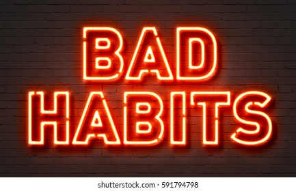 Bad habits neon sign on brick wall background