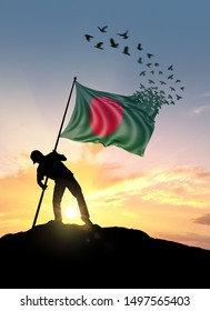 Bangladesh flag turn to birds while being planted by a man on a hill during sunrise.