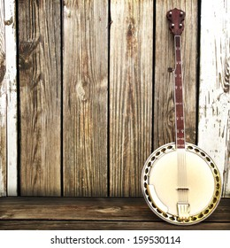 A Banjo leaning on a wooden fence. Advertisement with room for text or copy space.