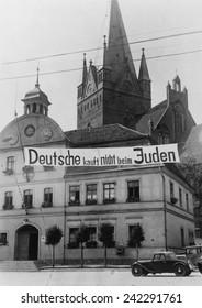Banner reading 'Deutsche kauft nich beim Juden' (Germans don't buy in Jewish shops) suspended over a street in Greifenberg, Pommerania (now Poland). 1935.