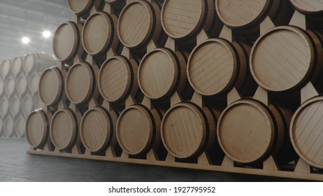 Barrels of wine, whiskey, bourbon liqueur or cognac in the basement. Aging of alcohol in oak barrels in warehouse. Wine, beer, whiskey casks stacked in a cellar, 3D illustration