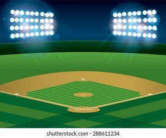 A baseball or softball field illuminated at night.