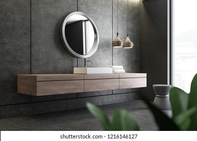 Bathroom corner with concrete walls and floor and white angular sink standing on wooden countertop with round mirror above it. 3d rendering
