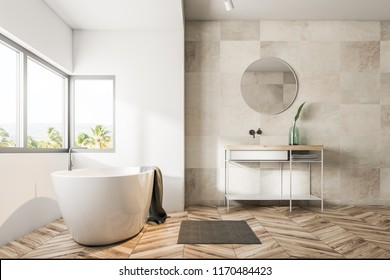 Bathroom interior with beige tile walls, a wooden floor, a bathtub under a large window, a sink and a round mirror. 3d rendering