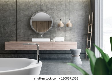 Bathroom interior with concrete walls and floor and white angular sink standing on wooden countertop with round mirror above it. Ladder in the corner. Bathtub in the foreground. 3d rendering