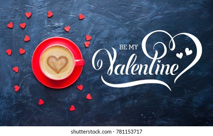 Be My Valentine hand lettering inscription. Cup of coffee with heart shape on dark blue background for Valentine's Day greeting card.