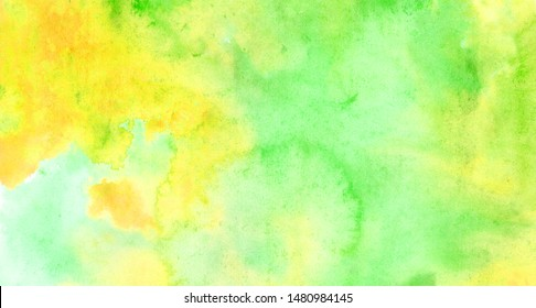 Beautiful abstract smudges of yellow green and aqua colors in hand painted watercolor background