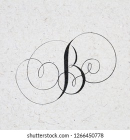 Beautiful calligraphy letter B with flourishes on kraft paper