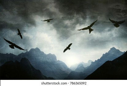 Beautiful gothic illustrative image in backlight of a mountain range with several hawks flying in a dramatic sky in a texture effect