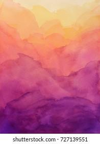 Beautiful hues of yellow gold pink and purple in hand painted watercolor background design with paint bleed and fringing in colorful sunrise or sunset colors in abstract cloudy mountain shapes.