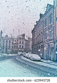 Beautiful winter in European city.  Daytime street scene with snowfall, houses and cars. Lille, Nord-Pas-de-Calais, France. Vertical colored Illustration in engraving style.