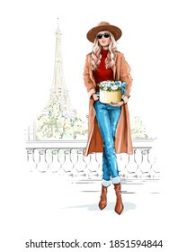 Beautiful woman in hat. Fashion lady in sunglasses. Stylish girl holding flower box and standing near Eiffel Tower.