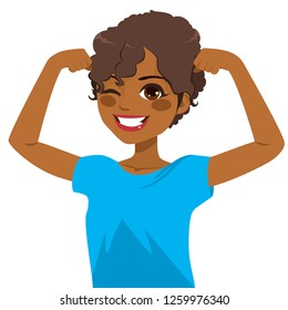 Beautiful young strong powerful African American girl winking eye and showing her muscles with blue shirt