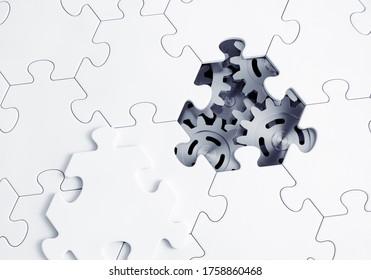 Derrière le puzzle. Les engrenages métalliques d'un mécanisme abstrait sont visibles à travers une pièce vide d'un puzzle. Graphiques de rendu 3D.