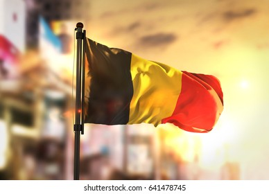 Belgium Flag Against City Blurred Background At Sunrise Backlight 3D Rendering