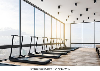 Big modern gym in skycraper with light interior, black treadmills, and wooden floor at sunrise. Health concept. 3D Rendering