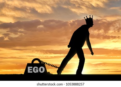 A big weight in the form of an ego is chained to the foot of a selfish and narcissistic man with a crown on his head. The concept of egoism as a problem interfering with living a full life