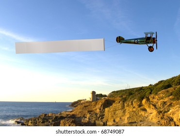 biplane pulling a blank banner on the beach