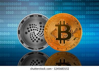 Bitcoin (BTC) and IOTA (MIOTA) coin on the binary code background; bitcoin vs iota