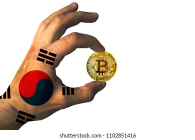 Bitcoin crypto currency South Korea flag Isolated Golden Coin of Bitcoin in the Republic of Korea flag hand between two fingers shows OK sign on a white background