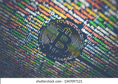 Bitcoin logo among programmer code in blue yellow and green colors. Photo of a screen with blockchain computer code. blue background.