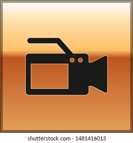 Black Cinema camera icon isolated on gold background. Video camera. Movie sign. Film projector