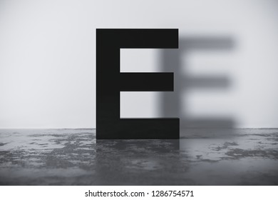 black letter E bold and uppercase casts a shadow on the white wall standing on the black floor. 3d render