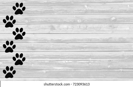 Black paw prints on white wooden background with copy space for text.