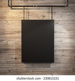 Black poster hanging on leather belt on wood background