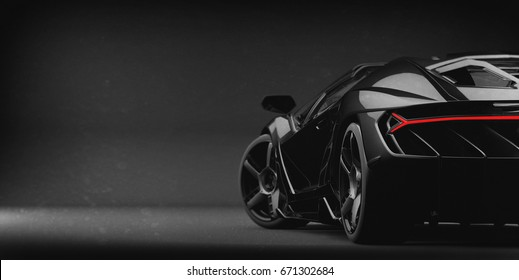 Black sports car (with grunge overlay, brandless), tail lights detail - 3d illustration