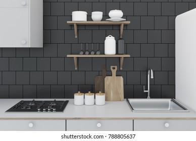 Black Tiled Kitchen Interior With White Countertops, Built In Appliances,  And A Cutting Board