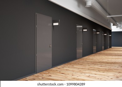 Black wall office or college corridor with rows of closed doors. Mock up signposts above the doors. A wooden floor. A side view. 3d rendering