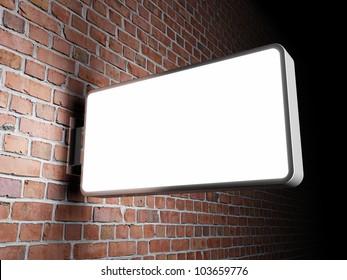 Blank advertising billboard on brick wall at night