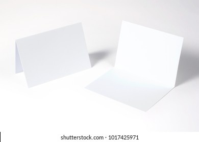 Blank bi-fold invitation, greeting cards isolated on white to showcase your event presentation. 3d illustration.