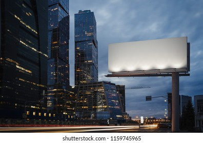 Blank billboard at night time in the city next to skyscrapers and road with lights on the frame. 3d rendering