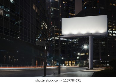 Blank billboard at night time during twilight with the city on background. 3d rendering