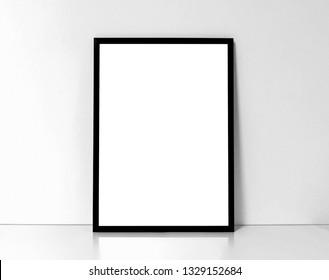 Blank black framed poster on a white interior background, mock up