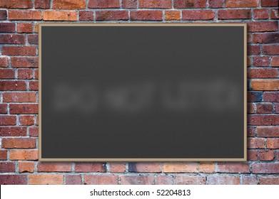 A blank blackboard against a brick wall.