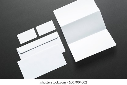 Blank business cards, letterheads and envelopes on dark textured background. Clean 3d illustration to showcase your presentation.