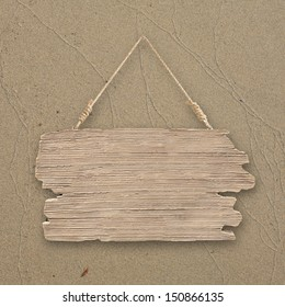 Blank hanging wood sign on sand background for beach concept