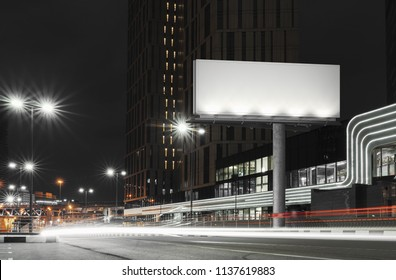 Blank illuminated billboard near well-lit road at night time in the city. 3d rendering