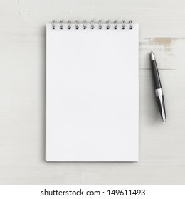 blank notebook on a white wooden table