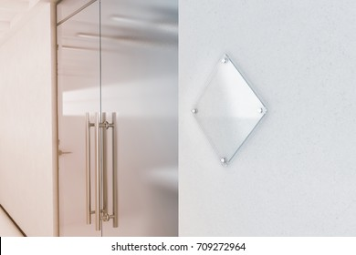 Blank rhombus transparent glass sign plate mock up, 3d rendering. Nameplate mockup on the wall near office entrance interior. Signage panel, store door template. Clear printing board for branding.