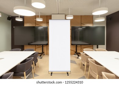 Blank roll up banner stand in modern office meeting room with blank presentation screens. With clipping path around ad banner. 3d illustration