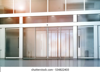 Blank sliding glass doors entrance mockup, 3d rendering. Commercial building entry mock up. Office exterior outdoor template. Emporium facade on sunset, front view. Sunny shopping center.
